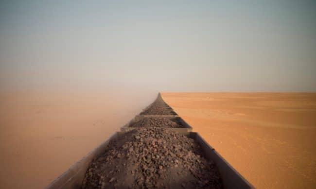 Une image prise du haut du dernier wagon d'un train transportant du minerai de fer en Mauritanie alors qu'il effectuait son périple de 700 km ; depuis la ville côtière de Nouadhibou jusqu'à la région de Zouérat dans le Sahara. Long de 2,5 km, ce train est l'un des plus grands au monde, il compte plus de 200 wagons chargés de minerai. – © Adrian Guerin, Australia, Winner, Open, Travel, 2020 Sony World Photography Awards.