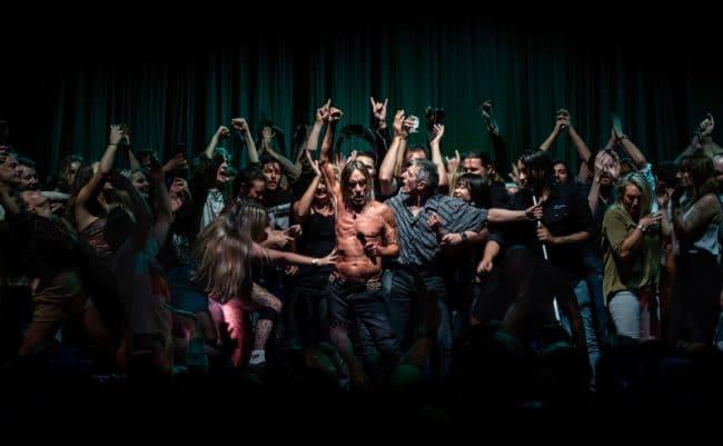 Un instantané du moment où le public a été invité à venir danser sur scène lors d'un concert d'Iggy Pop à l'Opéra de Sydney le 17 avril 2019. L'image représente Iggy Pop au milieu d'une foule de fans en délire : le chanteur se trouve sous les feux de la rampe alors qu'une femme réussit à le toucher et un assistant essaie de tenir les danseurs à distance. La scène, mise en parallèle avec un tableau du Caravage, évoque un passage biblique : « Car elle disait : Si je touche ne serait-ce que ses vêtements, je serai sauvée » (Marc 5:25-34). – © Antoine Veling, Australia, Winner, Open, Culture, 2020 Sony World Photography Awards